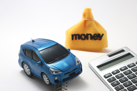 Toy car, money, calculator and notebook on white background