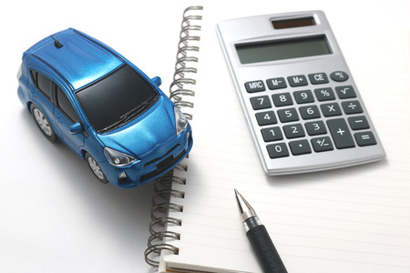 Toy car, calculator, pen and notebook on white background. Banque d'images