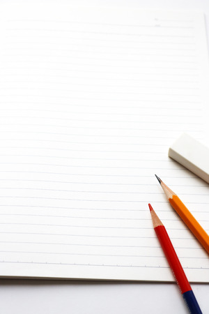 red pencil: Blank notebook with pencil, red pencil and eraser on white background.