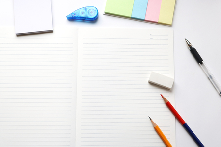 Blank notebook with pencil, red pencil, pen, tag papers, notepad, correction tape, and eraser on white background.