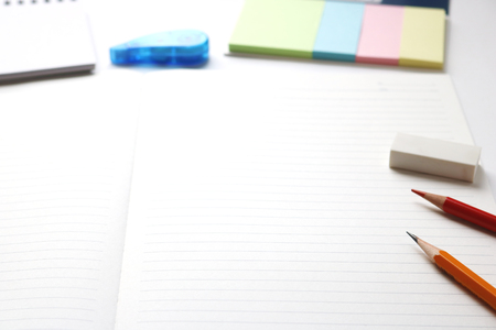 red pencil: Blank notebook with pencil, red pencil, tag papers, notepad, correction tape, and eraser on white background. Stock Photo