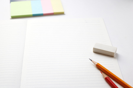 red pencil: Blank notebook with pencil, red pencil, tag papers, and eraser on white background. Stock Photo