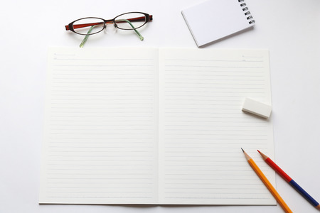 red pencil: Blank notebook with pencil, red pencil, notepad, glasses, and eraser on white background.