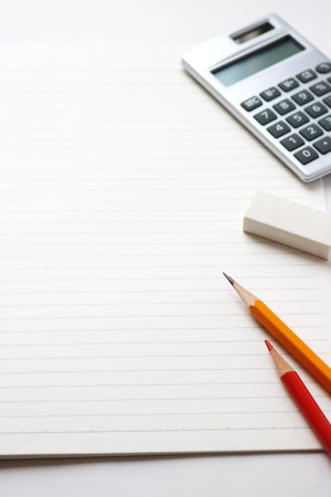 red pencil: Blank notebook with pencil, red pencil, calculator, and eraser on white background. Stock Photo