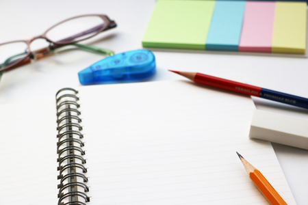 red pencil: Blank notebook with pencil, red pencil, tag papers, correction tape, glasses, and eraser on white background.