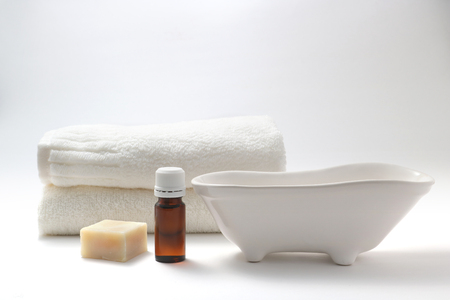 Aroma oil bottles, soap, a bathtub figurine, and towels on white background.