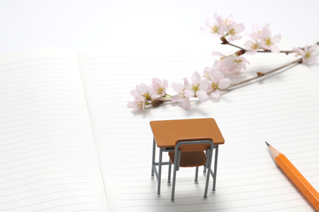 Study desk and cherry blossoms on the notebook. Stock Photo