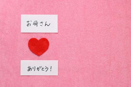 日本語でお母さんをありがとうございます。赤い手の心と書かれた文字スペルお母さんありがとうございます日本語で。 写真素材
