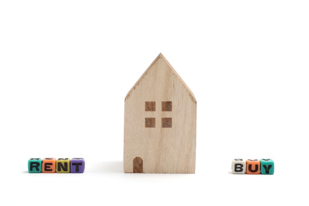 Miniature houses with alphabet blocks that spell buy and rent on white background. Concept of choice between buying and tenancy.