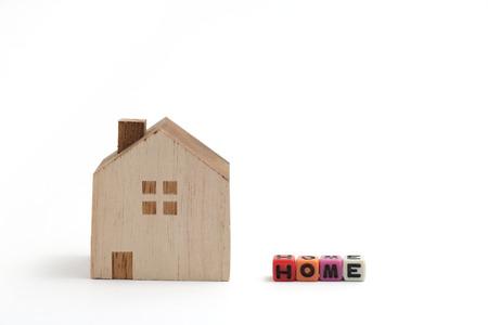 alphabet blocks: Miniature house with alphabet blocks that spell home on white background.
