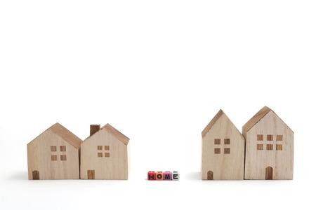 alphabet blocks: Miniature houses with alphabet blocks that spell home on white background.