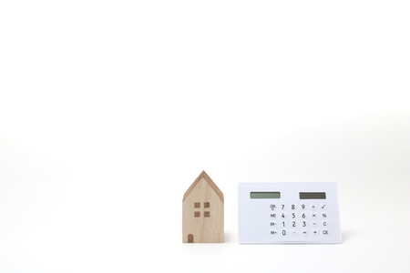 Miniature house and calculator on white background. Banque d'images