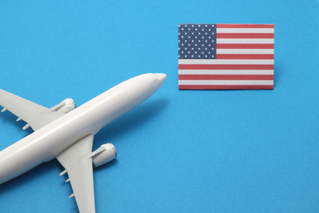 air travel: Trip by airplane to United States of America. Miniature airplane flies toward the flag of United States of America.