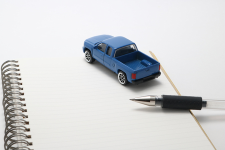 mail order: Toy car truck and pen on notebook. Stock Photo