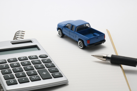 Toy car truck, calculator, notebook, and pen.