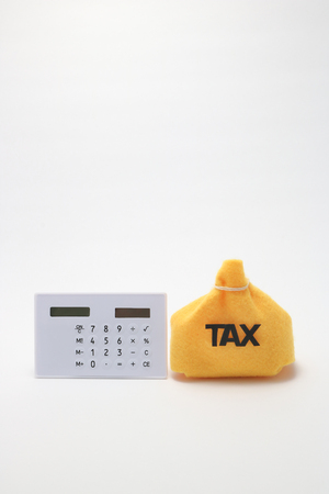 Tax and the bag calculator on white background. Stock Photo