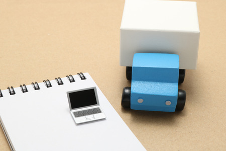 memo pad: Toy car and truck and miniature laptop on memo pad.
