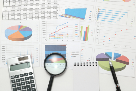 Pen, business items, and business documents with numbers and charts. Concept of workplace of the businessman.