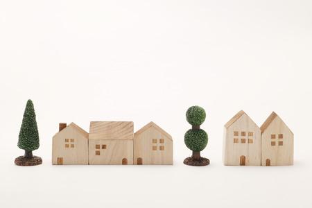 ミニチュアの家や白い背景の樹木します。ビルディング ブロックの行に配置できます。 写真素材