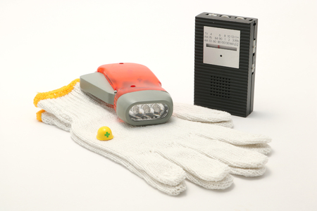Helmet, portable radio, work gloves, and flashlight on white background. Emergency goods.