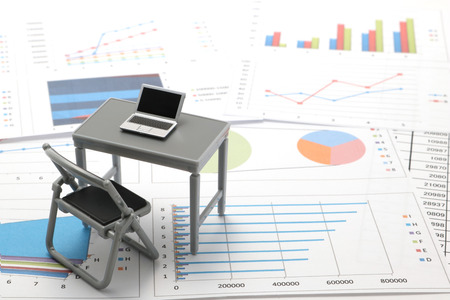 Notebook PC and business documents with numbers and charts. Concept of workplace of the businessman. Stock Photo