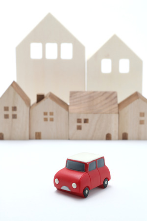 shared sharing: Miniature car and houses on white back ground.