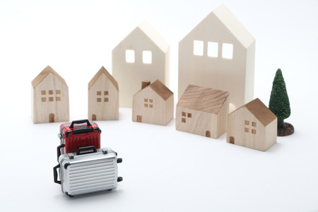 rentals: Houses and suitcases on white background. Vacation rentals, renting private homes and rooms. Stock Photo