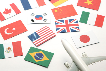 Trip by airplane. Miniature airplane go toward national flags of many countries.