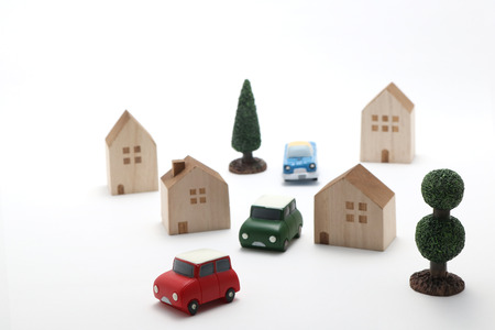 Houses, cars and trees on white background. Cityscape of toys.