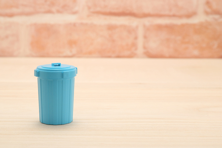 put away: Blue plastic garbage bin in front of brick wall.
