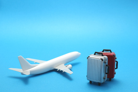Miniature toy airplane and suitcases on blue background. Trip by airplane.