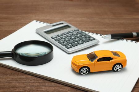 Spielzeugauto, Lupe, Taschenrechner, Stift und Notizbuch. Mieten, kaufen oder Kfz-Versicherung Konzept. Standard-Bild