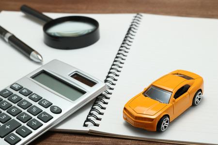 おもちゃの車、虫眼鏡、電卓、ペン、ノート。家賃、購入や保険車のコンセプト。