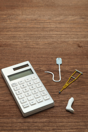 critical care: Miniature items of illness or injury beside calculator.