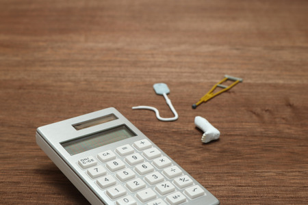 critical care: Miniature items of illness or injury beside calculator. Injury, illness, medical, insurance concept. Stock Photo