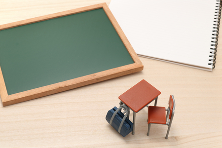 Miniature blackboard, notebook, desk, and school bag on wood. Stock Photo