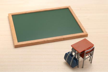 Miniature tableau noir, un bureau et sac d'école sur bois.