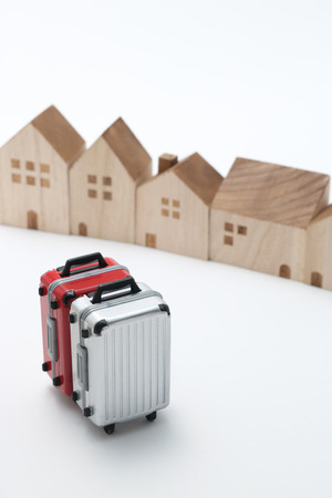 Houses and suitcases on white background. Vacation rentals, renting private homes and rooms. Banque d'images