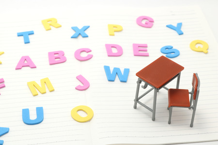 Alphabet letters and miniature study desk on white background. English education concept.