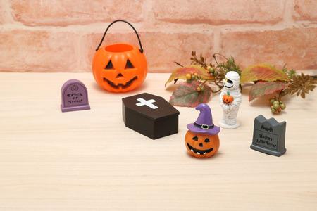 Halloween pumpkin Jack O  lantern, graves, mummy, autumn leaves and coffin on wood. Stock Photo