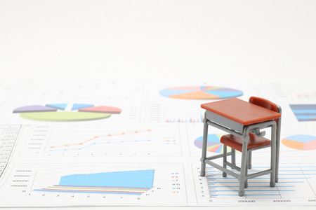 Miniature school study desk and documents with charts and graphs. Concept of math study.