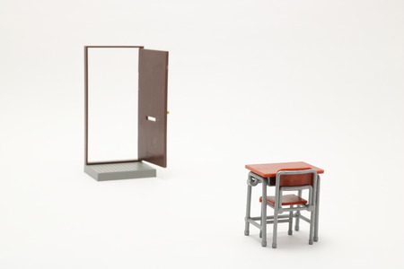 Miniature of brown open door and school study desk on white background. Stock Photo