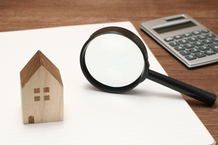 Miniature house, magnifying glass, calculator, pen and notebook. New house concept. Stock Photo