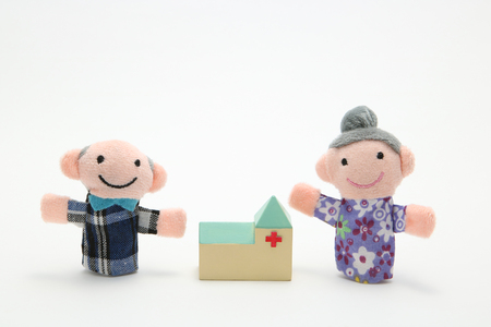 photgraphy: Puppet of the old couple and hospital on white background. Nursing care.