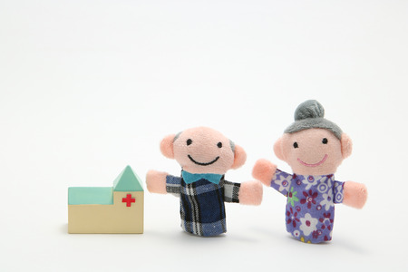 phisical: Puppet of the old couple and hospital on white background. Nursing care.