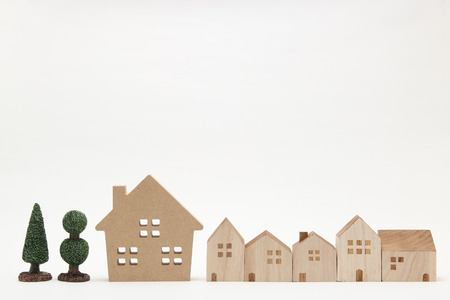 housing lot: Miniature houses and trees on white background. Building blocks arranged in row.