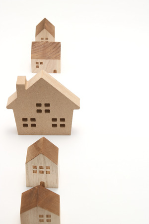 housing lot: Miniature houses on white background. Building blocks arranged in a row. Stock Photo