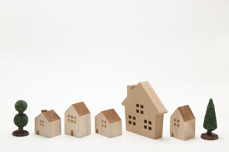 housing lot: Miniature houses and trees on white background. Building blocks arranged in a row.