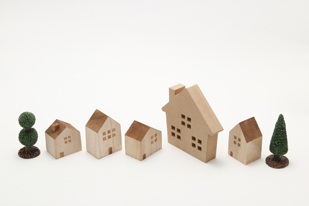 Miniature houses and trees on white background. Building blocks arranged in a row.