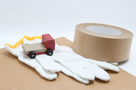 hauler: Toy mini car truck, packing tape, card boards, and cotton work gloves on white background. Distribution concept. Stock Photo